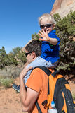Father and son hiking. Father holding his son on the shoulders hiking Royalty Free Stock Images