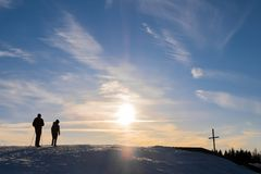 Father and son hiking mountain summit cross with nice sunset. Father and son hiking on snowy mountain Schoeckl to summit cross with nice sunset in Austria Royalty Free Stock Photography