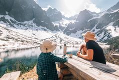 Father and son hiking traveler rest and drink tea near the mount. Ain lake royalty free stock photography