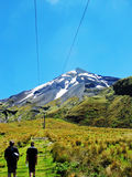 Father & son hiking up track to snowy mountain NZ Royalty Free Stock Photography