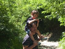 Father with son on his shoulders comes down from a forest path o. N a summer day Stock Photo