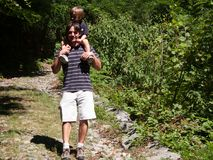 Father with son on his shoulders comes down from a forest path o. N a summer day Royalty Free Stock Photo