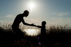 Father and son hold hands and look at each other against the background of the sunset by the sea. Silhouettes of father and son hold hands and look at each other Royalty Free Stock Photo