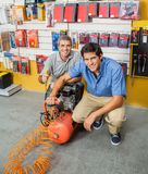Father And Son Holding Air Compressor In Store Stock Image
