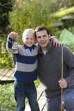 Father and son holding bug net and specimen jar outdoors Stock Photo