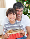 Father and son holding a Christmas gift Stock Photos