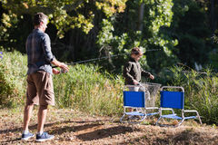 Father and son holding fishing equipment in forest. On sunny day stock image