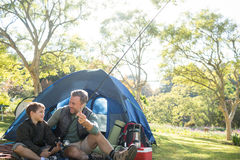Father and son holding a fishing rod outside the tent. While fly fishing stock images