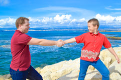 Father and son holding hands. With sea and clouds in the background. They are happy, love and respect each other. They are standing on the stone wave-breaker Stock Images