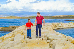 Father and son holding hands. And walking together with sea and clouds in the background. They are happy, love and respect each other. They are walking on the Stock Photo