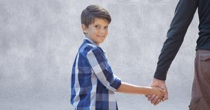 Father and son holding hands against grey wall. Digital composite of Father and son holding hands against grey wall Royalty Free Stock Image