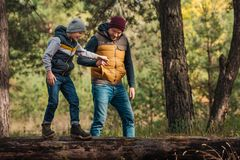 Father and son holding hands while boy. Walking on log in forest Royalty Free Stock Photo