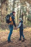 Father and son holding hands and smiling at camera while. Hiking together Stock Image