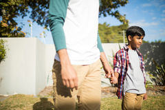 Father and son holding hands during sunny day. Father and son holding hands while standing in yard during sunny day Stock Photos