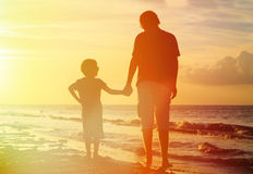 Father and son holding hands at sunset. Sea Royalty Free Stock Image