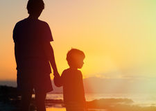 Father and son holding hands at sunset stock images