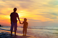 Father and son holding hands at sunset stock image