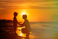 Father and son holding hands at sunset. Sea Royalty Free Stock Images