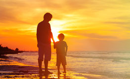 Father and son holding hands at sunset sea. Silhouettes of father and son holding hands at sunset sea Royalty Free Stock Image