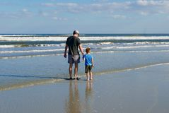 Father and son holding hands while walking on the beach. Father and son are holding hands as they walk along the shore of a Florida, USA beach Stock Photo