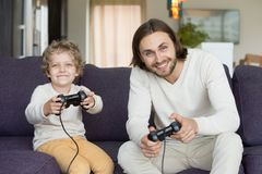 Father and son holding joysticks playing video games at home. Father and son holding joysticks controllers sitting on sofa looking at camera, dad with little boy royalty free stock image