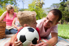 Father and son holding a soccer ball. With their family reading in the background at a picnic Royalty Free Stock Images