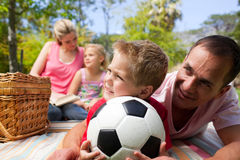 Father and son holding a soccer ball. At a picnic Stock Photography