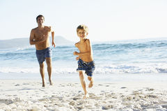 Father And Son On Holiday Running Along Beach Stock Photos