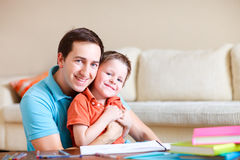 Father and son at home. Young father and his son drawing and reading together stock photography