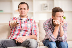 Father and son at home. Boy sitting at sofa and get bored while his father watching television Royalty Free Stock Image