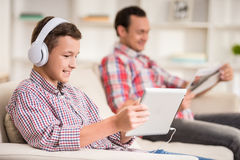 Father and son at home. Boy sitting at sofa at home and listen to music while his father reading newspaper royalty free stock photo