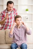 Father and son at home. Son closing ears while father scolding  him Royalty Free Stock Photo