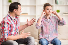 Father and son at home. Son closing ears while father scolding  him Stock Photography