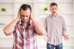 Father and son at home. Father and son dressed casual having quarrel at home Stock Photo