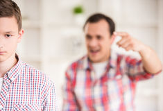 Father and son at home. Father and son dressed casual having quarrel at home Stock Photography
