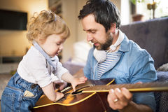 Father and son at home playing guitar together. Stock Photo