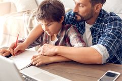 Father and son at home sitting at table doing assignment dad holding boy`s hand writing solution close-up royalty free stock photography
