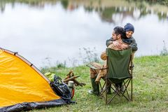 Father and son hugging in camping. Happy father and son hugging in camping with tent at lake Stock Images