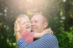 Father and son hugging. Father and son hugging and smiling in the garden. Masculinity concept Royalty Free Stock Images