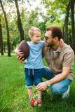 father and son hugging and holding american football ball
