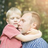 Father and son hugging. Father and little son hugging and smiling in the garden. Masculinity concept Stock Photos