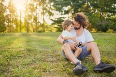 Father son hugging on the grass in the park. Father son hugging playing on the grass in the park. Father`s Day Stock Image