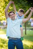 Father and son hugging and playing together in green nature on warm sunny summer evening. Concept of friendship between children. And parents, happy family royalty free stock photo