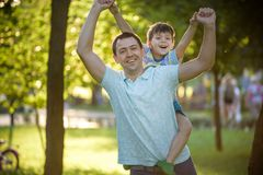 Father and son hugging and playing together in green nature on warm sunny summer evening. Concept of friendship between children. And parents, happy family stock photos