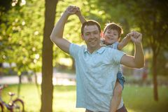 Father and son hugging and playing together in green nature on warm sunny summer evening. Concept of friendship between children royalty free stock photo