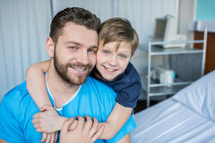 Father and son hugging while sitting on hospital bed. Dad and son in hospital Stock Photography