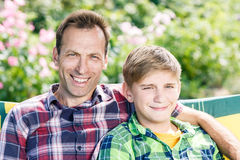 Father and son hugging sitting in the park Stock Image