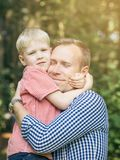 Father and son hugging. Father and son hugging and smiling in the garden. Masculinity concept. Blondy people. Family Stock Photos
