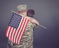 Father and Son Hugging after War Isolated. A young child is hugging his army soldier father and holding a usa flag. The child and dad are isolated on a blue Royalty Free Stock Image