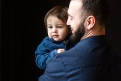 Dad smiles at his little child. Father and son in hugs at black background. Dad smiles at his little child Royalty Free Stock Image